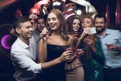 Une femme dans une robe noire chante des chansons avec ses amis à un club de karaoke Ses amis font le selfie Photo stock