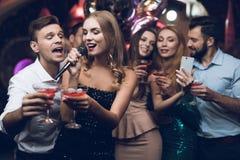 Une femme dans une robe noire chante des chansons avec ses amis à un club de karaoke Ses amis font le selfie Photos libres de droits