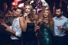 Une femme dans une robe noire chante des chansons avec ses amis à un club de karaoke Ses amis ont l'amusement sur le fond Photographie stock