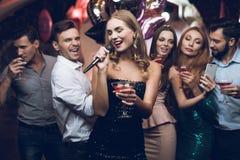 Une femme dans une robe noire chante des chansons avec ses amis à un club de karaoke Ses amis ont l'amusement sur le fond Image libre de droits