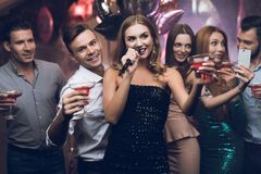 Une femme dans une robe noire chante des chansons avec ses amis à un club de karaoke Ses amis ont l'amusement sur le fond Photos stock