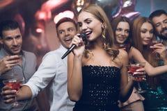 Une femme dans une robe noire chante des chansons avec ses amis à un club de karaoke Ses amis ont l'amusement sur le fond Images libres de droits