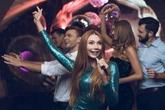 Une femme dans une robe verte chante des chansons avec ses amis à un club de karaoke Ses amis ont l'amusement sur le fond Photo libre de droits
