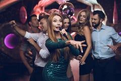 Une femme dans une robe verte chante des chansons avec ses amis à un club de karaoke Ses amis ont l'amusement sur le fond Images libres de droits