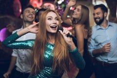 Une femme dans une robe verte chante des chansons avec ses amis à un club de karaoke Ses amis ont l'amusement sur le fond Photo stock