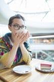 Une femme dans un café boit du café Photo stock