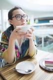 Une femme dans un café boit du café Photographie stock