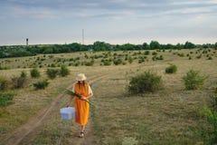 Une femme dans un chapeau de paille et un boîte-cadeau marche photographie stock libre de droits