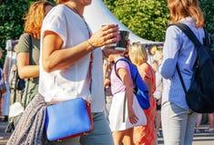 Une femme dans un chemisier blanc et avec un sac à main bleu élégant dans une grande ville photo stock
