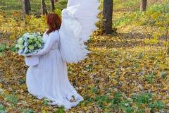 Une femme dans un costume blanc d'ange sur un fond du paysage d'automne images libres de droits