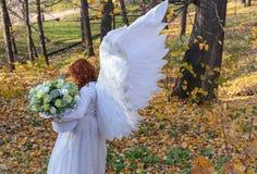 Une femme dans un costume blanc d'ange sur un fond du paysage d'automne images stock