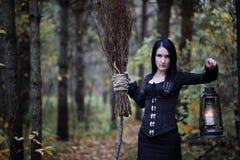 Une femme dans un costume de sorcière dans une forêt photographie stock
