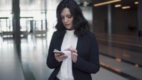 Une femme dans un costume marche par le lobby d'un immeuble de bureaux moderne la femme d'affaires utilise un téléphone portable banque de vidéos