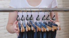 Une femme dans un magasin marche à un cintre avec le pantalon bleu de denim, les enlève tous et les prend clips vidéos