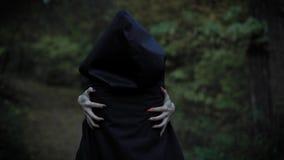 Une femme dans un manteau avec un capot s'embrasse derrière ses mains avec de longs clous, comme une sorcière, les promenades mys banque de vidéos
