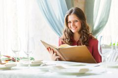Une femme dans un restaurant avec la carte dans des mains Images stock