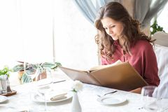 Une femme dans un restaurant avec la carte dans des mains Photo libre de droits