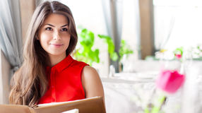 Une femme dans un restaurant avec la carte dans des mains Images libres de droits