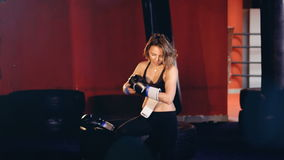 Une femme dans un studio de boxe met dessus des gants banque de vidéos