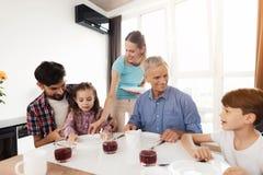 Une femme dans un T-shirt de bleu place ses plats avant ses parents avant qu'ils tous s'asseyent au dîner Photographie stock libre de droits