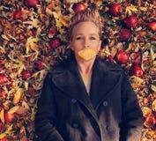 une femme dans une veste intéressante avec une feuille au-dessus de sa bouche s'étendant dans une pile des feuilles et des pommes image stock