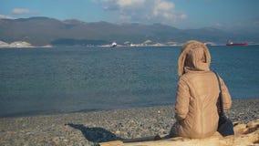 Une femme dans une veste avec un sac s'assied sur un rondin par la mer clips vidéos