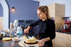 Une femme de confiseur fait le gâteau dans la cuisine photos stock