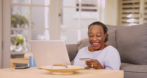Une femme de couleur plus âgée lui paye des factures sur son ordinateur portable image stock
