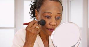 Une femme de couleur pluse âgé fait son maquillage pendant le matin dans sa salle de bains photo stock