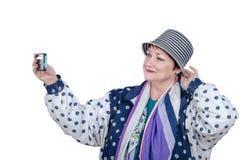 Une femme de déplacement plus âgée prend la photo de selfie dans le studio Photographie stock
