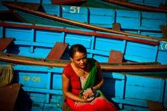 Une femme de Nepali s'asseyant dans les bateaux du lac Phewa, Pokhara, Népal Photos stock