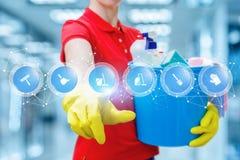Une femme de nettoyage dans les gants en caoutchouc maintient un seau accompli avec des produits chimiques et touche un écran ave image libre de droits