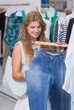 Une femme de sourire heureuse choisissant quelques vêtements images libres de droits