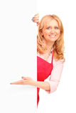 Une femme de sourire posant derrière un panell blanc Images stock