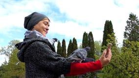 Une femme de sourire prend une photo des colombes se reposant sur sa main banque de vidéos