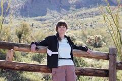 Une femme de sourire se penchant contre une barrière de rondin Photographie stock libre de droits