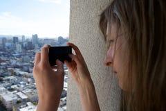 Une femme de touriste photographie une ville avec son téléphone portable Image stock