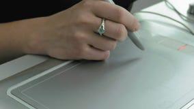 Une femme dessine avec le convertisseur analogique-numérique et le stylet de comprimé de stylo banque de vidéos