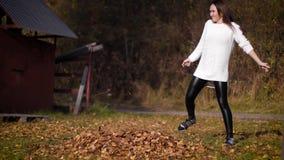 Une femme donne un coup de pied des feuilles en automne, les lançant partout La fille donne un coup de pied sur une pile des feui banque de vidéos