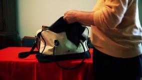 Une femme emballe des choses dans son sac banque de vidéos
