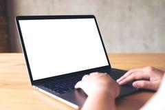 Une femme employant et dactylographiant sur l'ordinateur portable avec l'écran de bureau blanc vide sur la table en bois Images libres de droits
