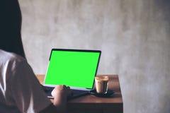 Une femme employant et dactylographiant sur l'ordinateur portable avec l'écran de bureau vide avec la tasse de café sur la table  Photo stock