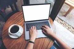 Une femme employant et introduisant au clavier sur l'ordinateur portable avec l'écran de bureau blanc vide sur la table en bois l Image stock