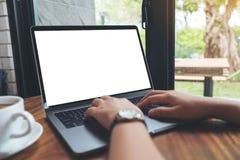 Une femme employant et introduisant au clavier sur l'ordinateur portable avec l'écran de bureau blanc vide sur la table en bois l Photographie stock