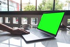 Une femme employant et introduisant au clavier sur l'ordinateur portable avec l'écran vide et la tasse de café sur la table le ca Photos stock