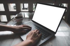 Une femme employant et introduisant au clavier sur l'ordinateur portable avec la tasse blanche vide d'écran et de café sur la tab Images stock