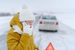 Une femme en hiver appelle aux services des urgences Image stock