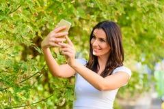 Une femme en parc prenant un Selfie avec son Smartphone Photos libres de droits