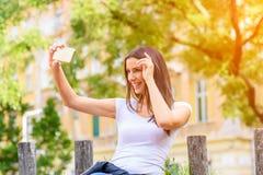 Une femme en parc prenant un Selfie avec son Smartphone Images libres de droits
