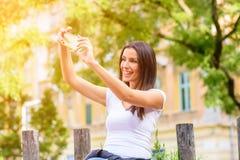Une femme en parc prenant un Selfie avec son Smartphone Photos stock